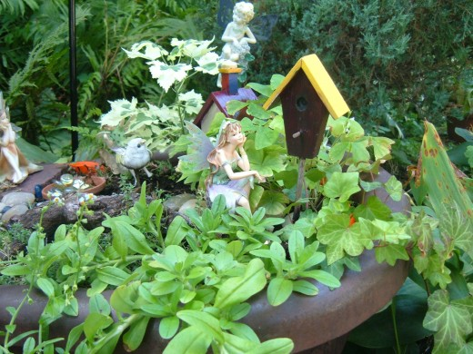 Our old rusted wagon offers quite a nice place for a fairy garden. It is off the ground, yet close enough.  Each year, I make something new in the wagon garden. It is a great container for this smaller garden.