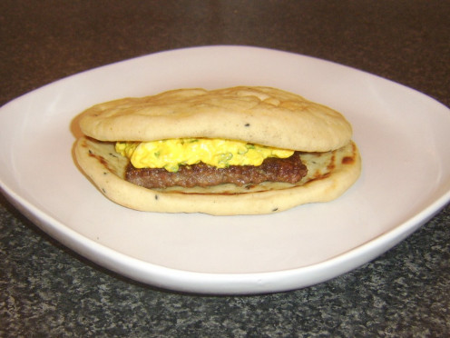 A curried Lorne sausage is topped with turmeric spiced egg in a naan bread sandwich