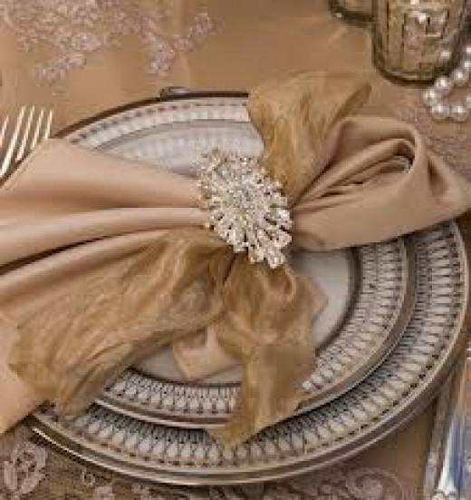 Wide fabric serviettes with a brooche and silver old school underplates look great.