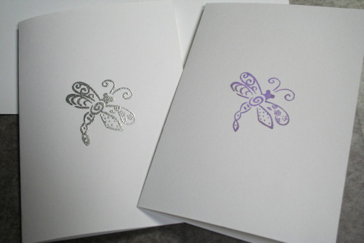 Card on the right is a stamped image from dye ink.  Card on the left is heat embossed with silver powder.