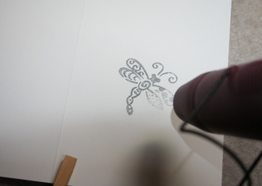 Using a heat gun to melt the embossing powder.