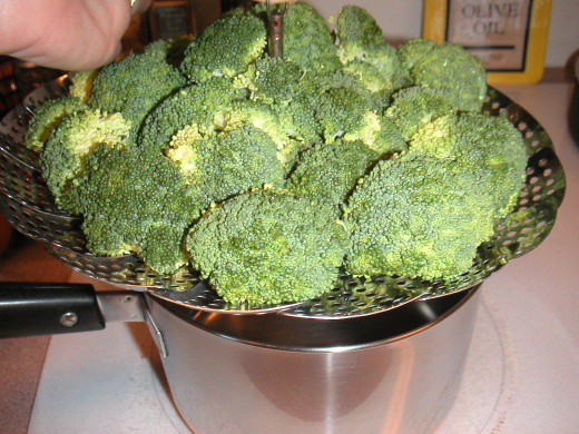 Move the metal steamer with the broccoli into the pan