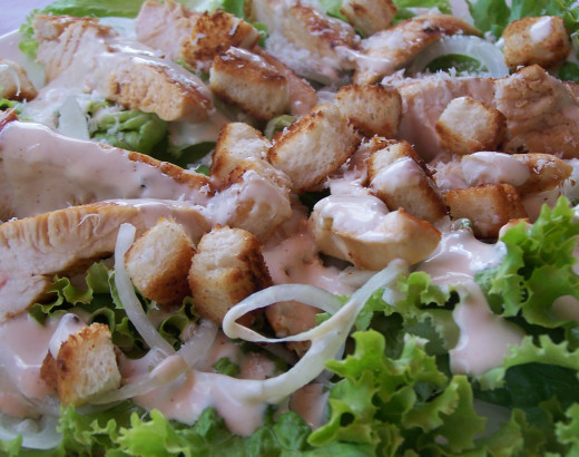 Chicken Caesar Salad: crisp lettuce, onion rings, chicken, croutons, cream dressing and parmesan shavings