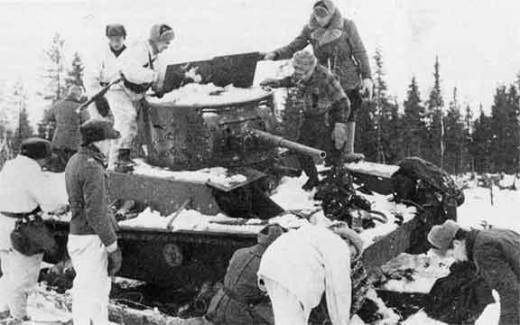 Finnish soldiers inspecting an abondoned Soviet T-26 tank after the Battle of Raate road.