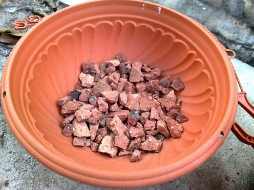These are pieces of brick at the bottom of the pot to improve drainage.