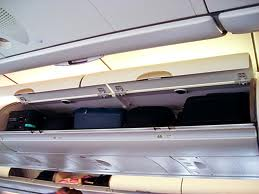 Hand luggage is stored in the overhead compartment on the plane.