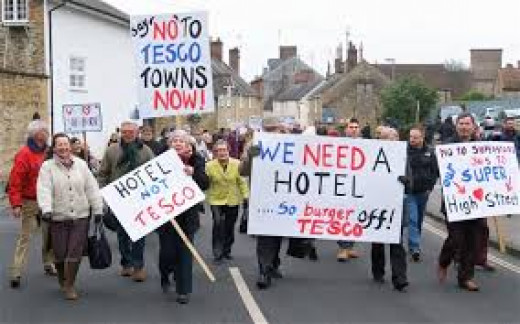 Protesters indicating they need other infrastructure before any more Tescos.