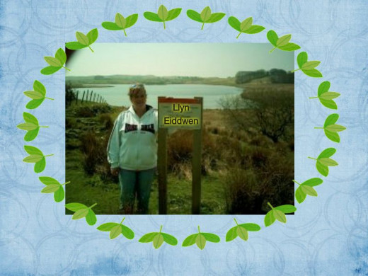 Me by the sign Llyn Eiddwen with the lake behind me.