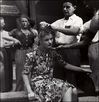 A horizontal collaborator has her head shaved by a group of resisters.
