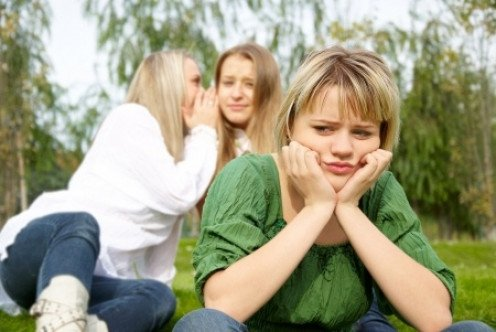 Two teenage girls whispering behind another girls back.