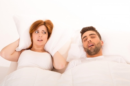 A woman covers her ears due to her husbands snoring problem.