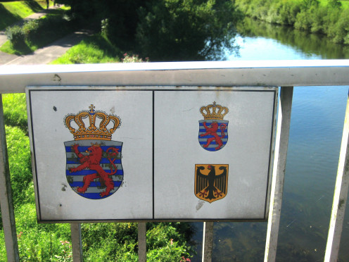 Sign at a bridge over the Sauer river, indicating Luxembourg-German border