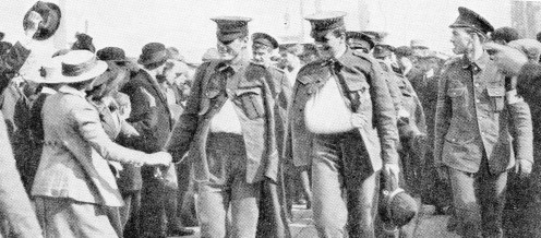 The two leaders belong to the Dorset Regiment. One has his left arm injured and the other his right. Bugler Clark (on the right), although wounded, would not part with his beloved bugle, and brought it home, accompanied by a German helmet.