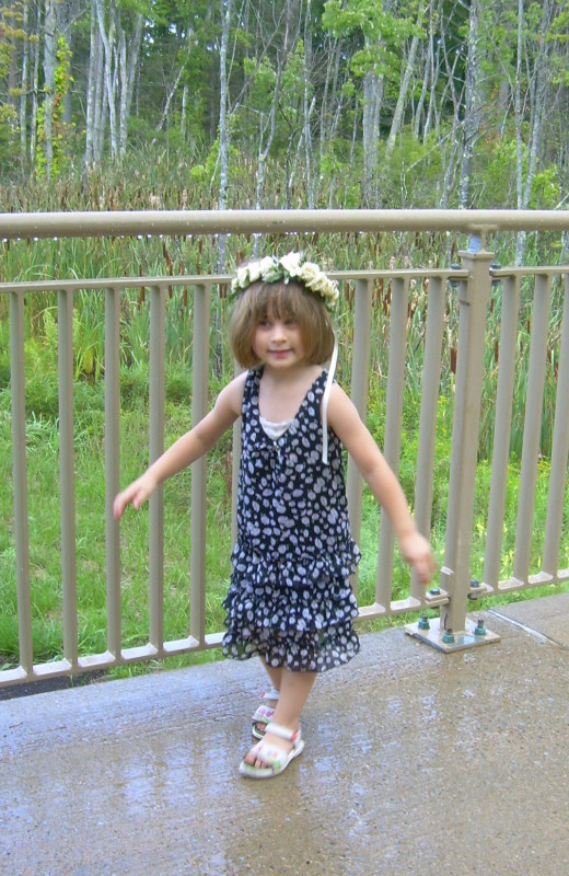 My daughter dancing in the rain with a garland of flowers on her head