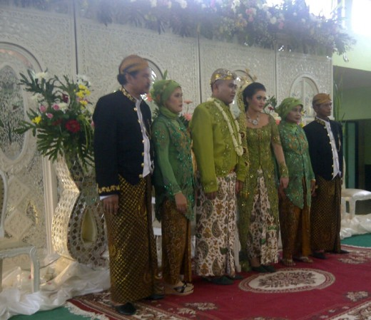 The bride and groom flanked by their parents in Javanese wedding costumes.