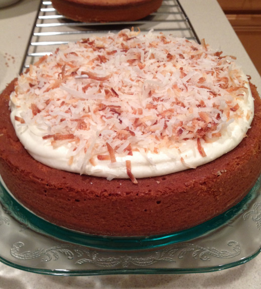 Place plenty of toasted coconut over the first frosted cake layer.