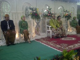 They sit on bridal chairs with parents take sitting positions next to their son/daughter in law.