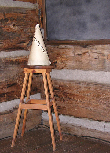 At one time, children were punished by being forced to sit in a corner of the classroom while wearing a dunce cap.