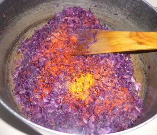 After adding cabbage in the oil, red chilies and turmeric powder is added and mixed.