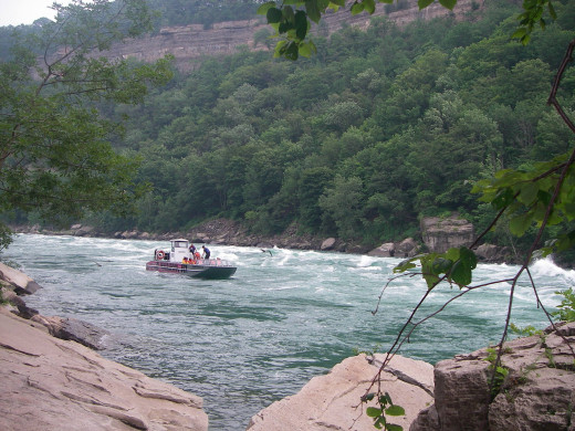 A jet boat fighting the current of Niagara River to go up to the Falls (As seen from Niagara Glen).