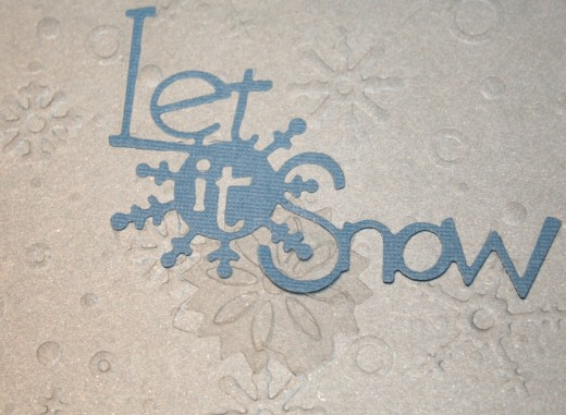 This design took several steps.  The base of the card was white cardstock.  The topper was silver cardstock embossed with a snowflake pattern.  I then layered a die cut phrase with a plastic snowflake to each card.