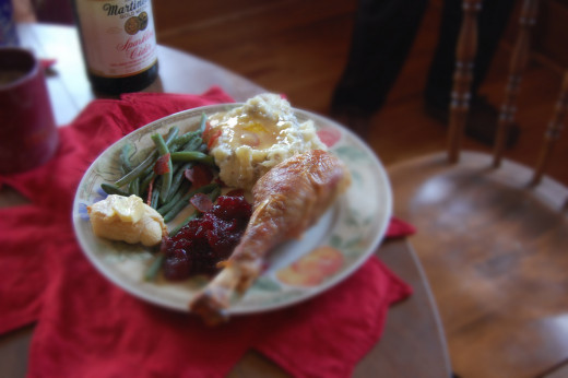 Thanksgiving dinner on a plate. Turkey leg, mashed potatoes with gravy, green beans, cranberry sauce and Pillsbury crescent rolls with butter.