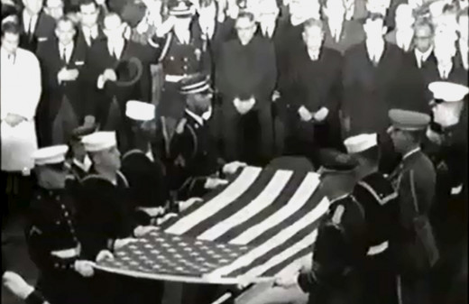 A military honor guard holds the flag above John F. Kennedy's casket.