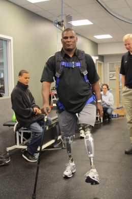 Lt. Col. Greg Gadson practices walking with his new prosthetic knees while his son, Jaelen, looks on. Lt. Col. Gadson is an above the knee amputee using next generation powered prosthetic limbs.