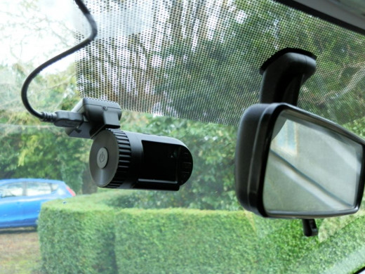Mini DVR 0801 dashcam situated behind rearview mirror
