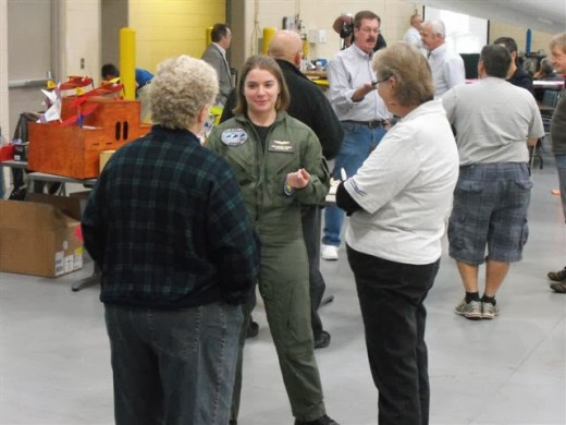 Anna Koerber, a 17 year old aviator, speaking with some attendees. Anna has accomplished flight of the T-6, the L-39, the Piper Warrior, and other aircraft and is ready for her career in aviation.