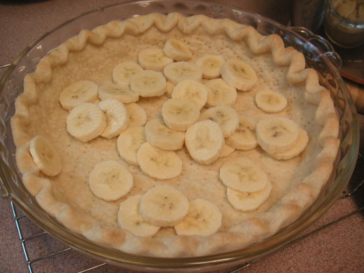 Peel and slice the bananas to cover the bottom of the baked crust