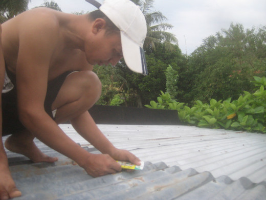 I sealed some spots of the roofing of our house before the storm (Photo Source: Ireno Alcala aka travel_man1971)