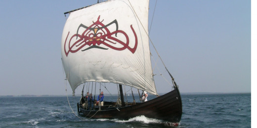 Knarr or trading ship setting out from Ribe under full sail for Jorvik
