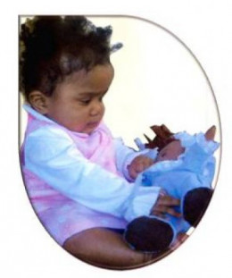 Baby observing her doll.