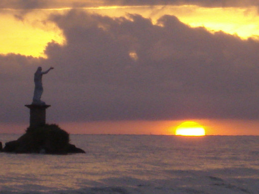 """On my 45th birthday I got to witness the Sunrise over the Caribbean Sea for the first time in my life.  Taken in Livingston, Guatemala.  This is the """"Statue of Liberty,"""" Garifuna people style!"""