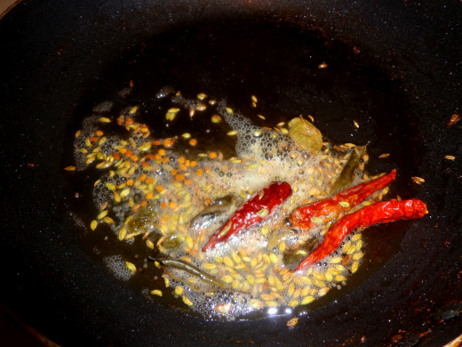 Cumin seeds, fenugreek seeds, fennel seeds and red chilies are getting fried in the oil