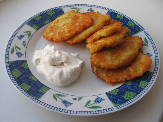 """Latkes"", infamous potato pancakes with sour cream."
