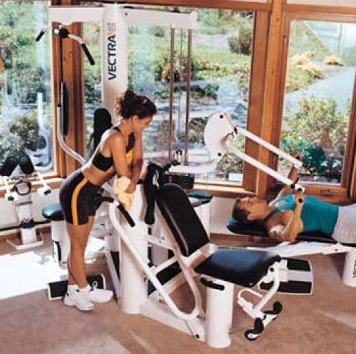 Home gym overlooking a garden with three large windows