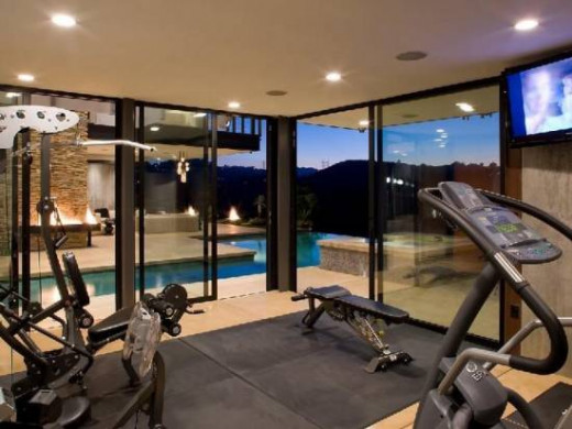 high ceilings, floor to ceiling windows with a view of an architecturally perfect swimming pool makes this home gym the ultimate in story book design