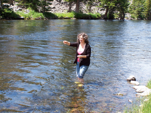 Can you write the perfect sentence to describe Bev standing in a river?