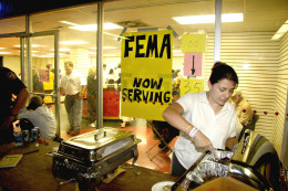 A volunteer serves hot meals to evacuees as they wait to register with FEMA at the Houston Astrodome. Thousands of people displaced by Hurricane Katrina are being housed in the Astrodome.