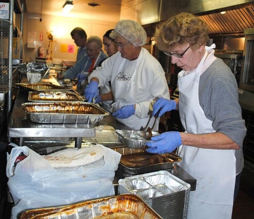 Volunteers work together to prepare Thanksgiving Day meals for people in need