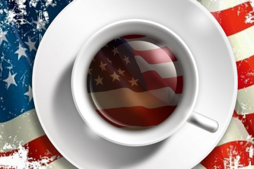 cup of coffee in white cup and saucer with coffee displaying American flag