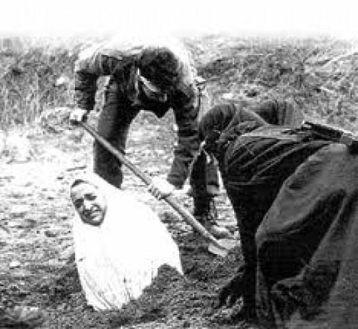 Woman being buried into the ground before a lapidation commences.