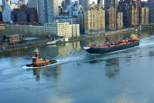 In a photograph that looks as much like a painting, Deborah Julian finds a powerful tugboat gliding in water that seems like syrup, guiding a tanker down the East River toward the Atlantic