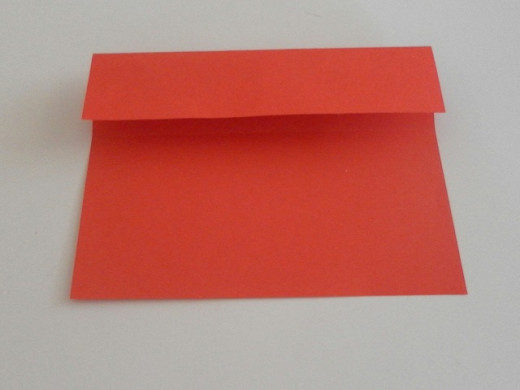 Align the top edge of the paper with the horizontal crease line and fold in half.
