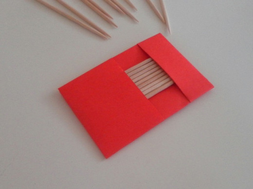 Carefully insert toothpicks into the origami case.
