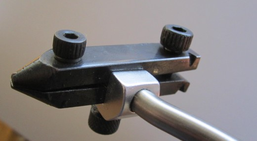 Pictured are the adjustment screws on the jaws.  The front screw near the jaws tips sets the jaws' width, while the back screw tightens the jaws.