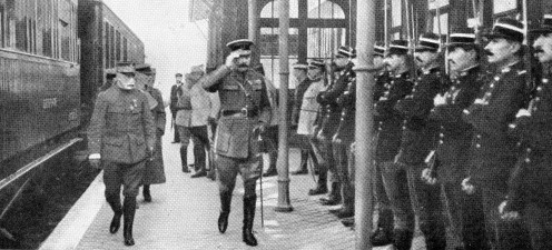 "Lord Kitchener arriving at a station ""somewhere in France "" on his way to visit the French Headquarters."