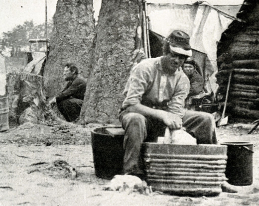 A soldier cleans his clothes in a metal tub